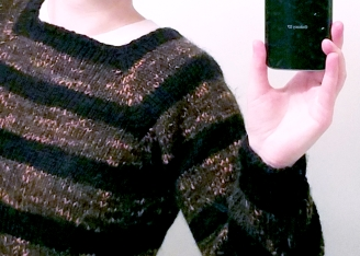 Close-up of the photoographer's torso wearing a sweater with a square neck and black-and-brownish-orangeish stripes.